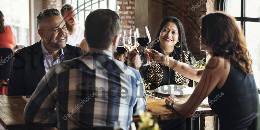Stock photo of cheerful people drinking wine - Cheerful people drinking wine in restaurant, celebration and beverages concept