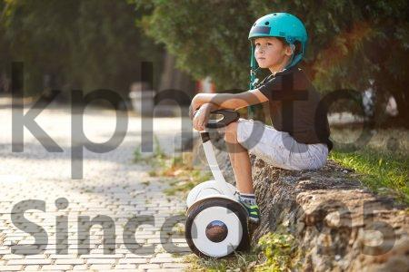 Stock photo of A boy riding a gyroboard in the park, a self-balancing scooter. Active lifestyle technology future. - A boy riding a gyroboard in the park, a self-balancing scooter. Active lifestyle technology future.