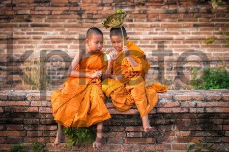 Stock photo of Two novice novices are looking and playing smartphone with funny in old temple at sunset time, Ayutthaya Province, Thailand - Two novice novices are looking and playing smartphone with funny in old temple at sunset time, Ayutthaya Province, Thailand