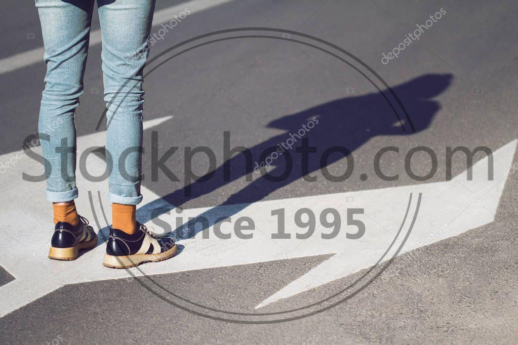 Stock photo of close up of woman shoes standing on the street - Side view close up of a young woman wearing black shoes and blue jeans standing on a street with arrow signs pointing in different directions concept for life choices
