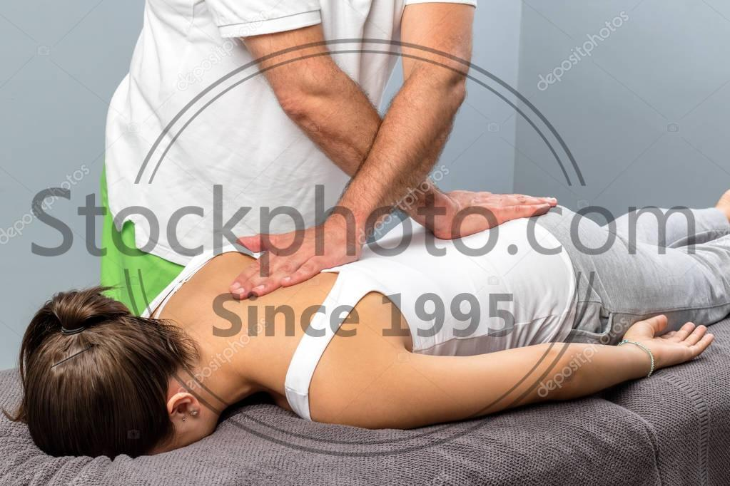Stock photo of Physiotherapist applying pressure on female spine. - Close up of male osteopath doing manipulative physical treatment on female spine.