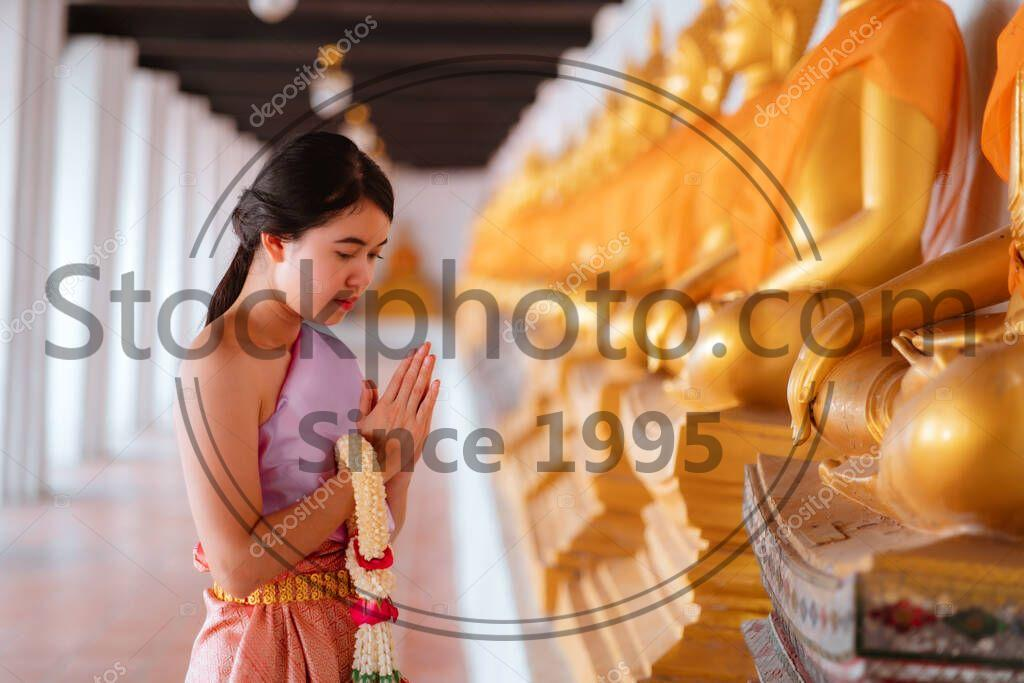 Stock photo of Asian women wearing Thai national costumes are worshiping Buddha images during Songkran Festival in Thailand . Thai New Year's Day. Thai tradition. - Asian women wearing Thai national costumes are worshiping Buddha images during Songkran Festival in Thailand . Thai New Year's Day. Thai tradition.