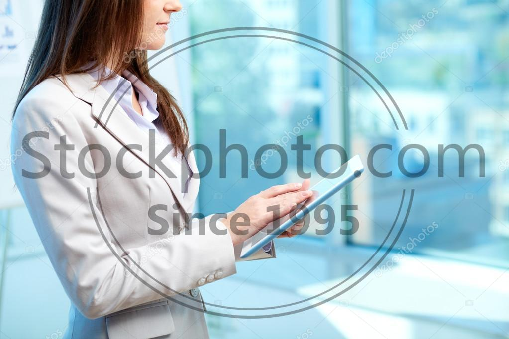 Stock photo of Networking - Close-up of businesswoman working with touchpad in office