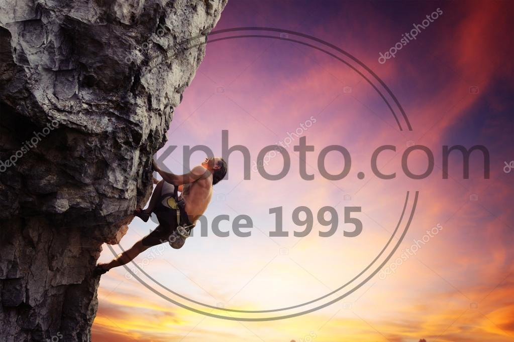 Stock photo of Climber - Young man climbing natural rocky wall with sunset sky on the background