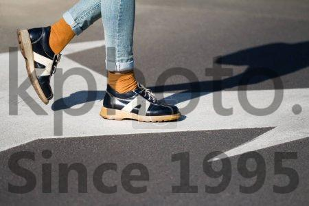 Stock photo of close up of woman shoes standing on the street - Side view close up of a fashionable young woman legs wearing black shoes and blue jeans walking from left to right on the street natural daylight