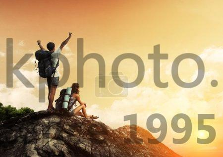 Stock photo of Hikers - Two hikers with backpacks enjoying sunset view from top of a mountain
