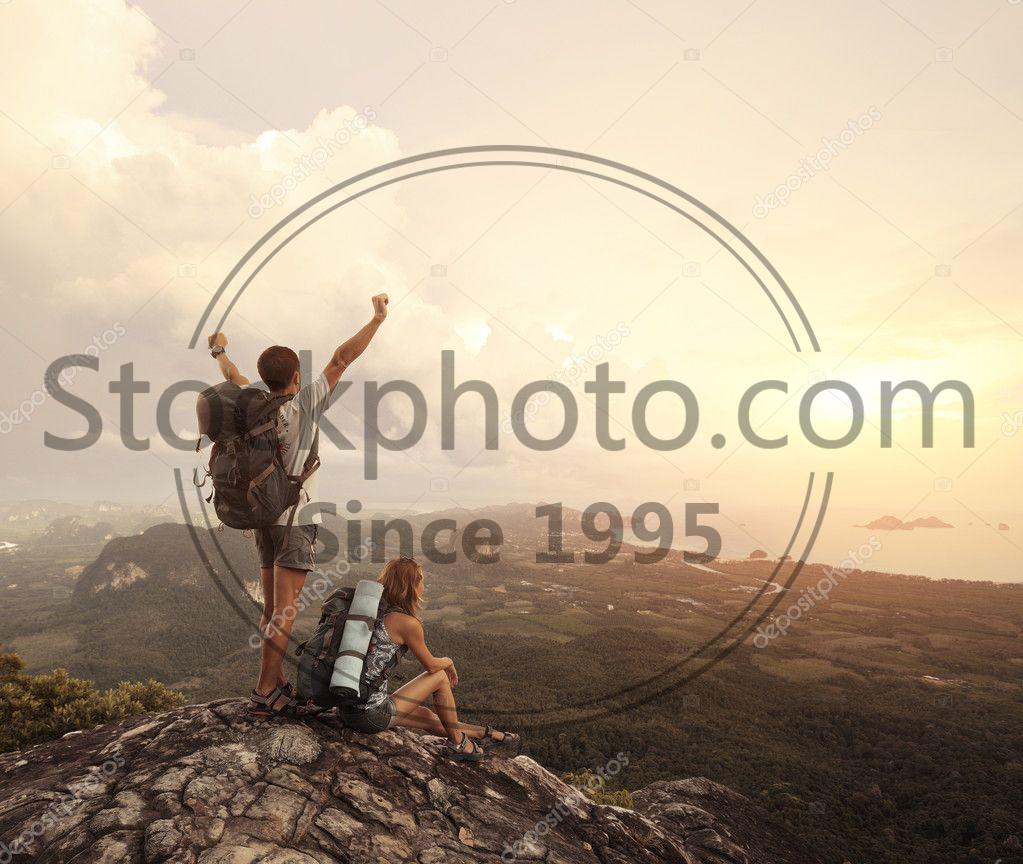 Stock photo of Hikers - Two hikers with backpacks standing on top of a mountain with great valley view