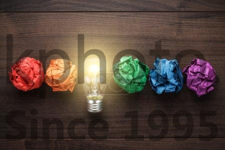 Stock photo of Great idea concept - Great idea concept with crumpled colorful paper and light bulb on wooden table