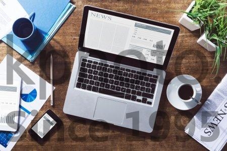 Stock photo of Financial news online - Financial business news online on a laptop with coffee and stationery